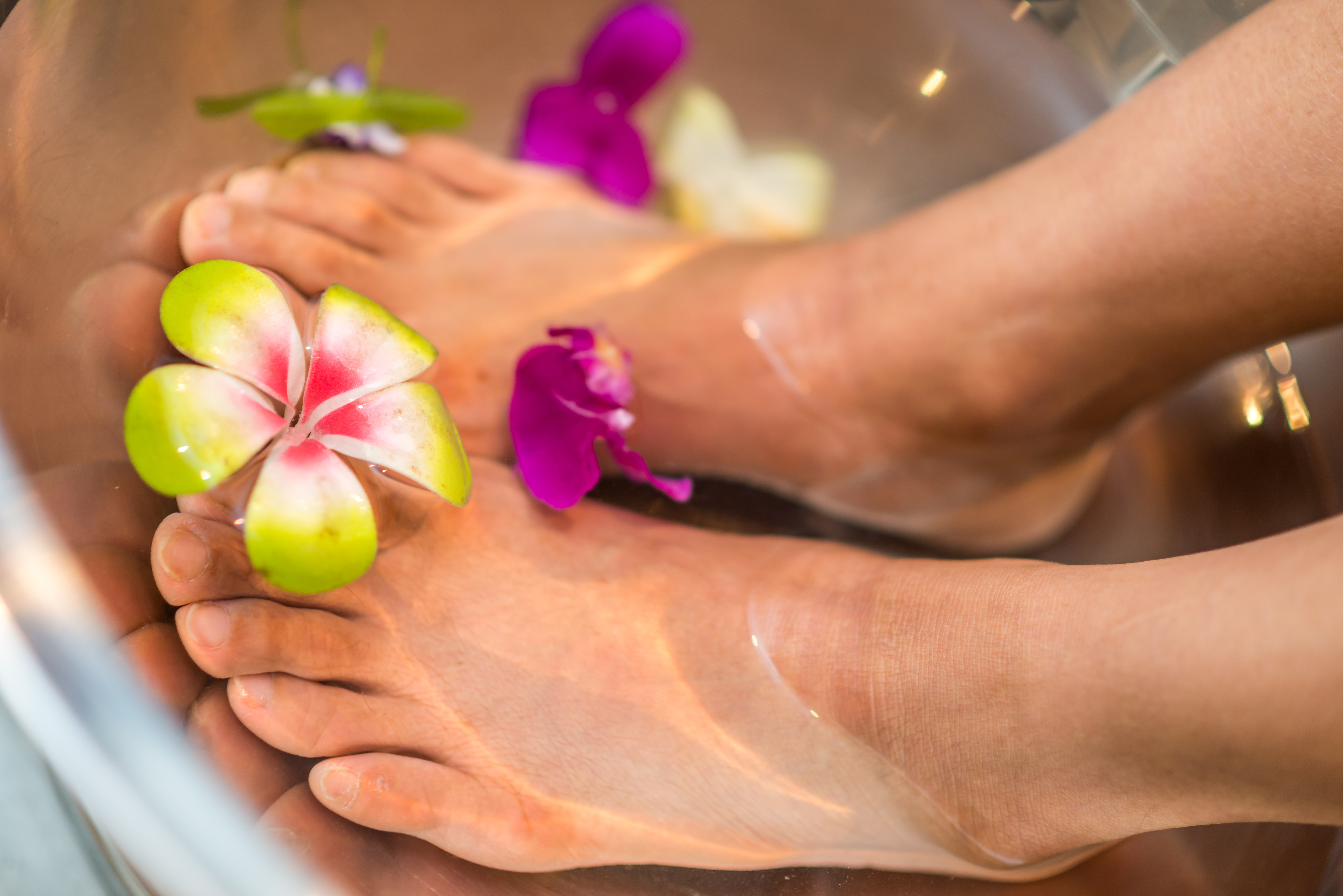 Feet in a basin of water with flowers.
